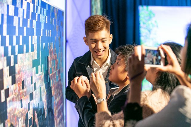Campaign supporters contribute to a photo mosaic at the Hong Kong tour event.